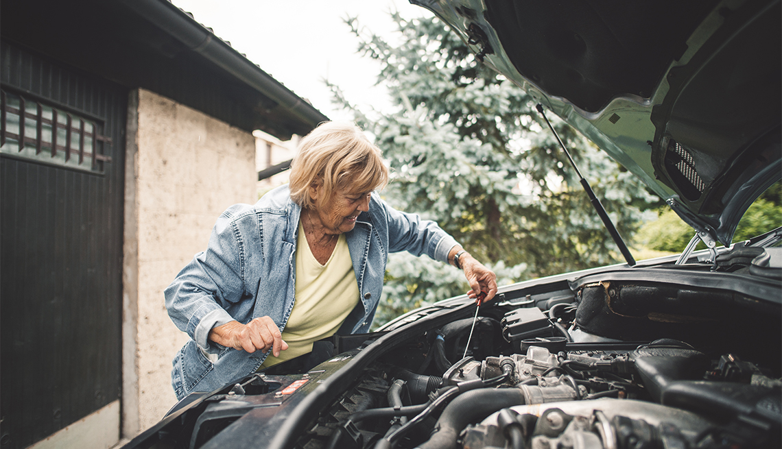 Woman checking oil level in car engine