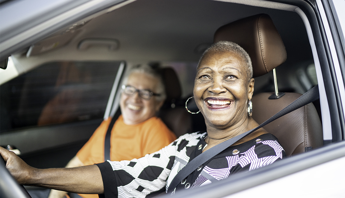 woman driving a car with a friend in the passenger seat