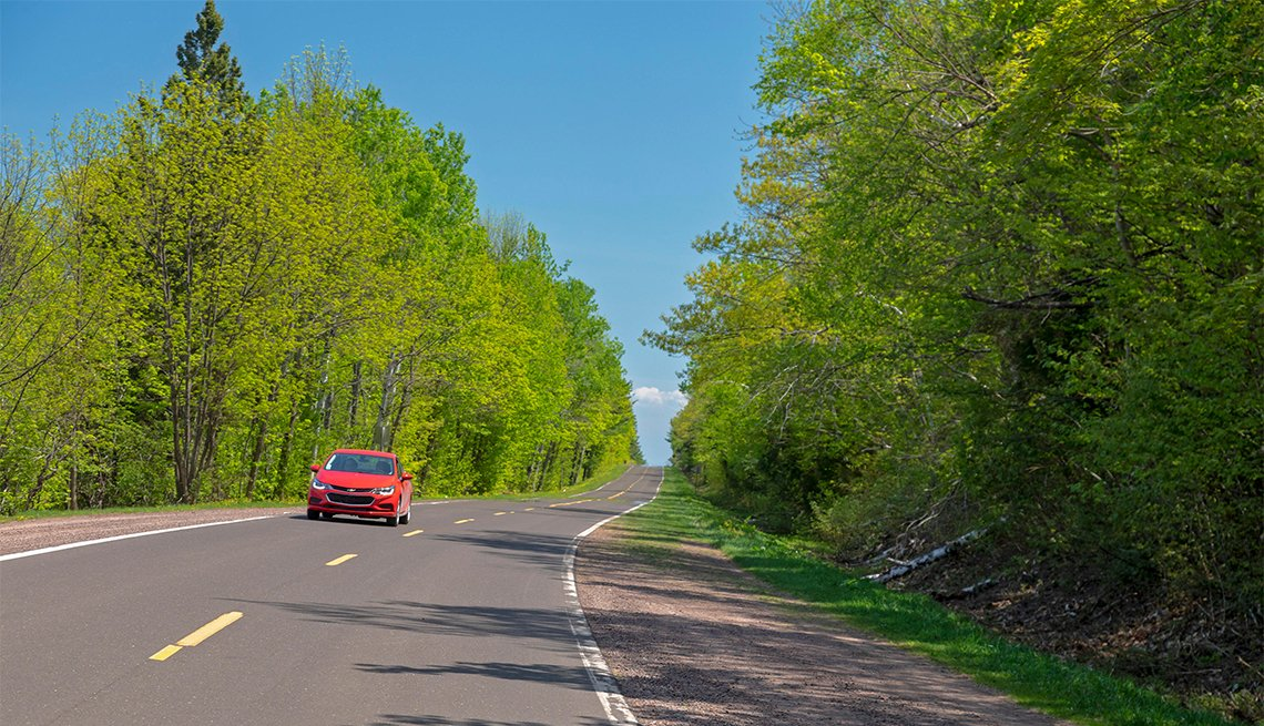 red car on Highway 107 in Porcupine Mountains Wilderness State Park