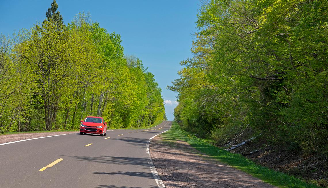 Auto rojo en la autopista 107 en Porcupine Mountains Wilderness State Park
