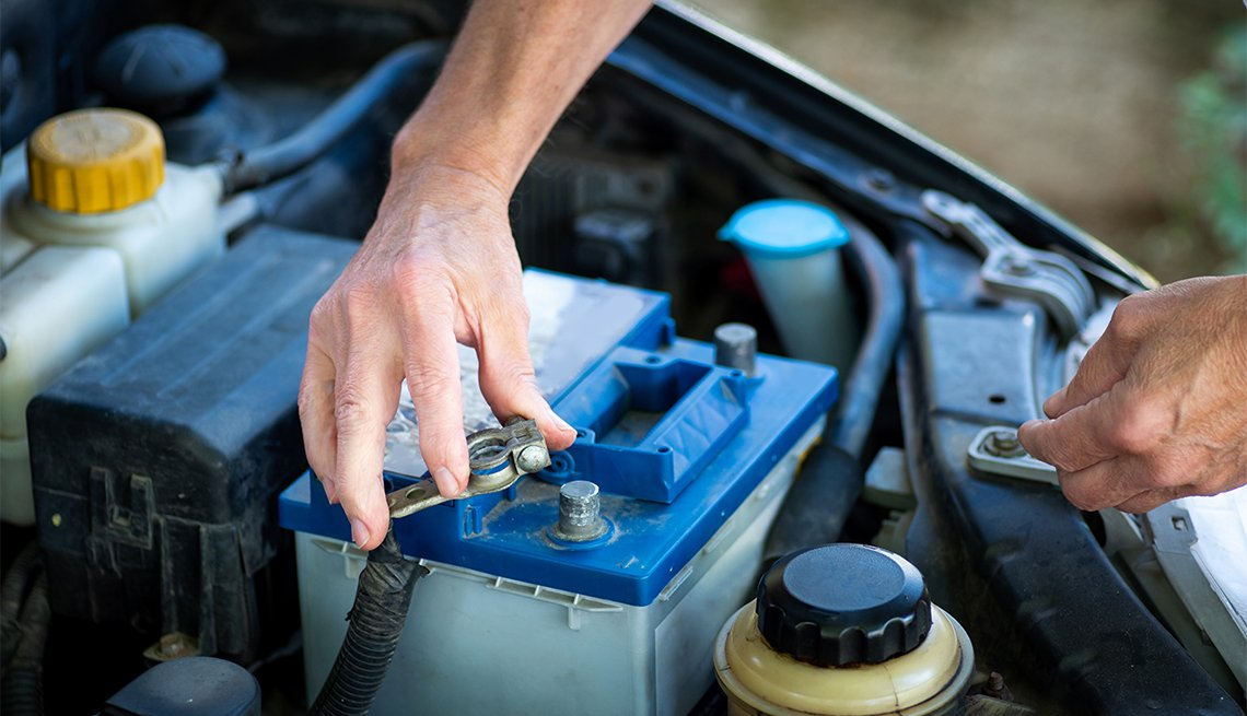 Man connecting the car battery to the vehicle with a wrench