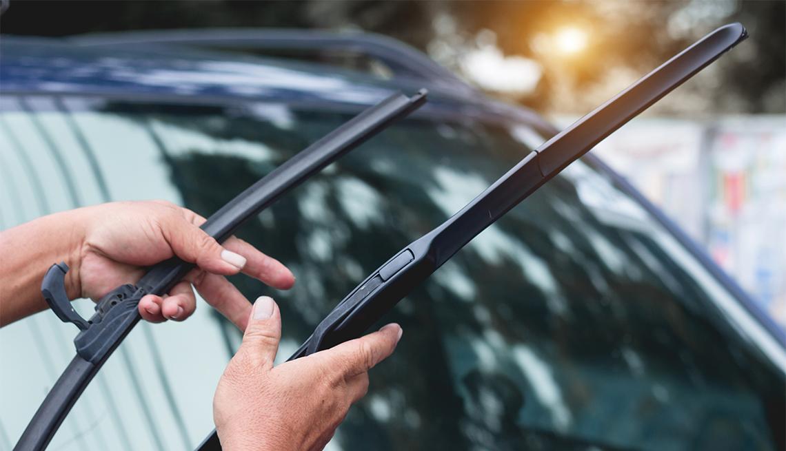 Persona ajusta las escobillas del limpiaparabrisas de un auto