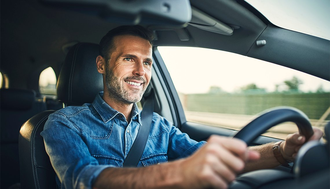 smiling man driving a car