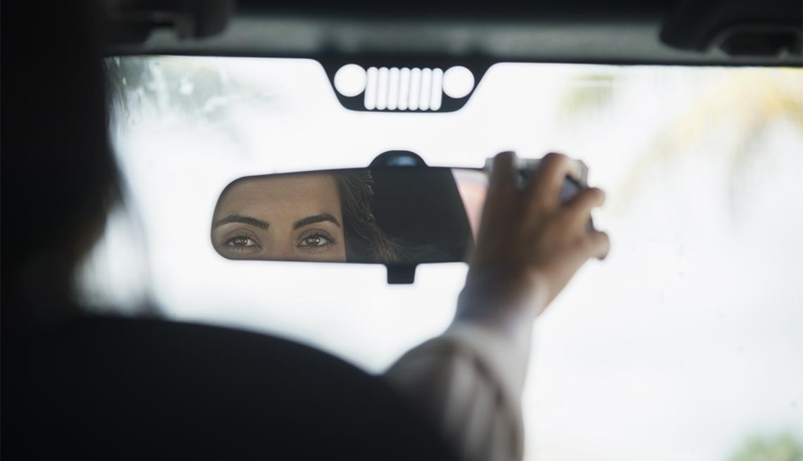Mujer ajustando el espejo retrovisor de su auto