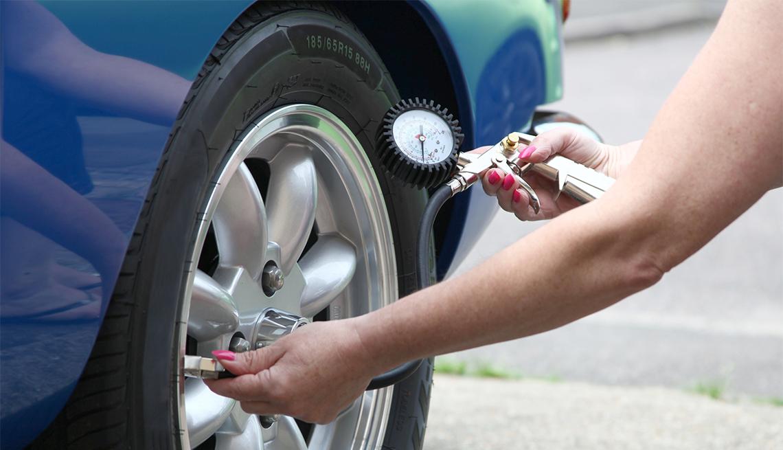 Mujer revisa la presión de aire de los neumáticos de un auto