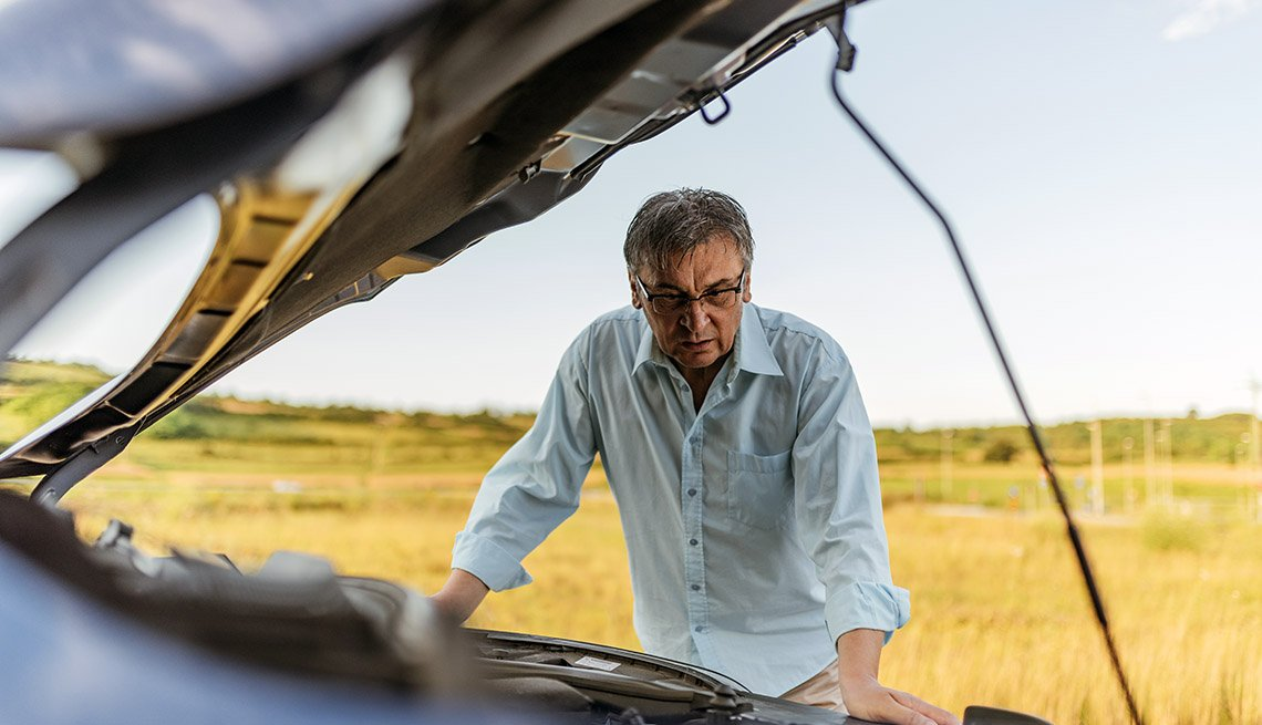 stressed man man leans over open hood of car checking engine after breaking down on the road