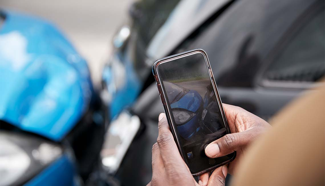 Male motorist involved in car accident taking pictures