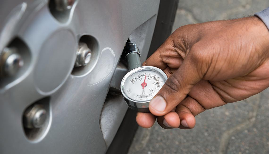 Una persona revisa la presión de la llanta de su auto