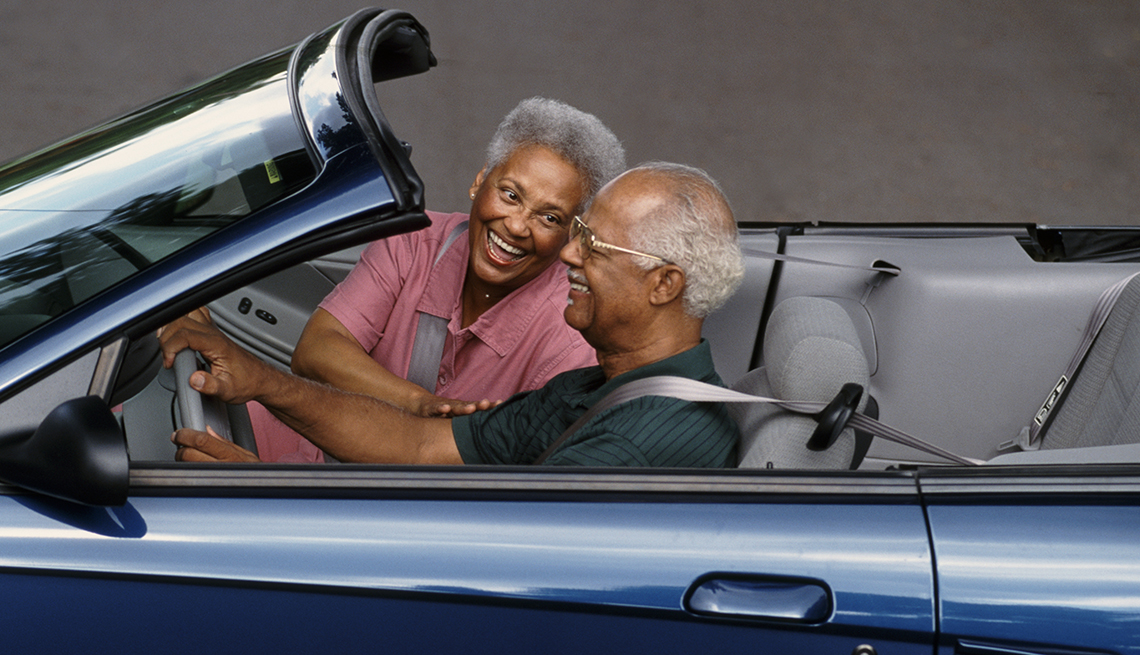 a man and woman drive in a car