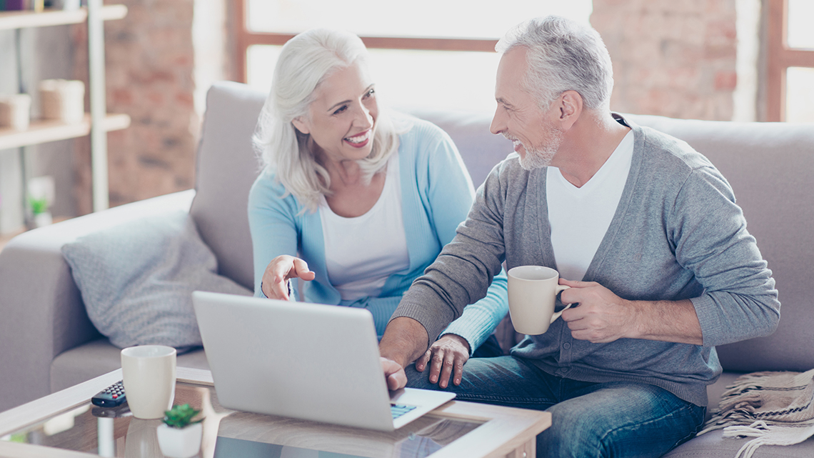 Two elderly people are sitting at home at the weekend, drinking coffee and watching films using the computer on the table, the woman is pointing on the monitor