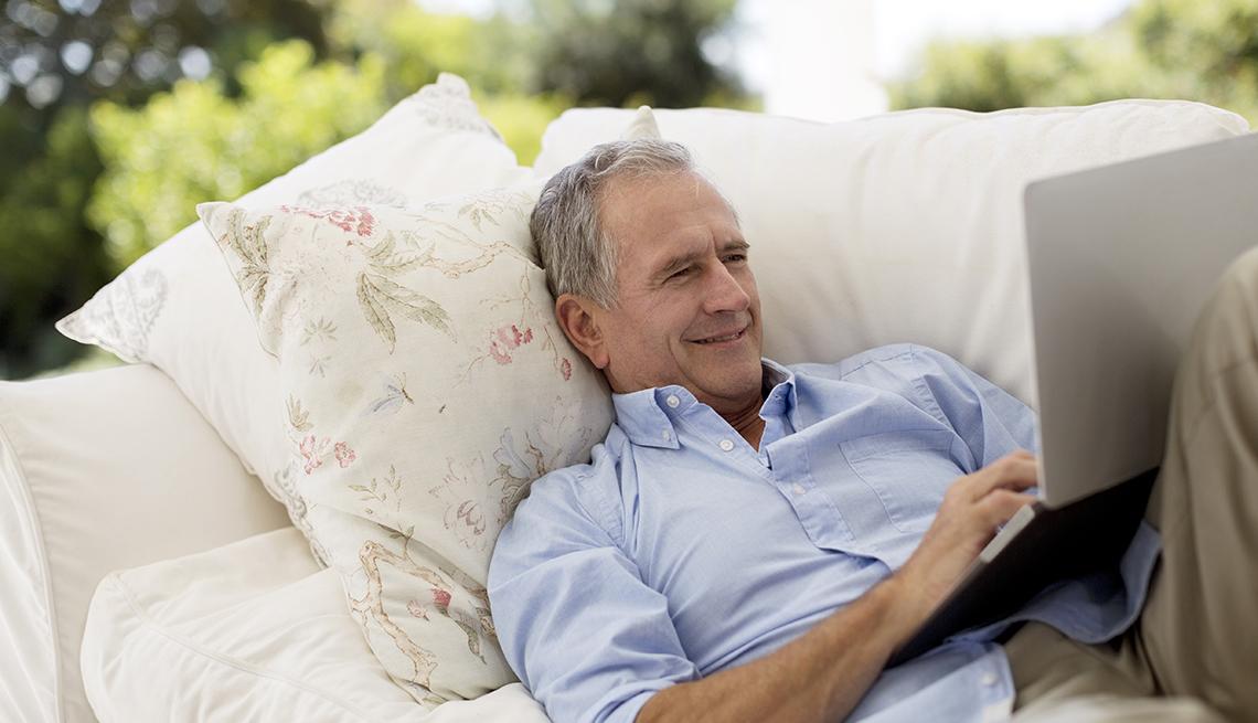 Senior man using laptop on patio sofa