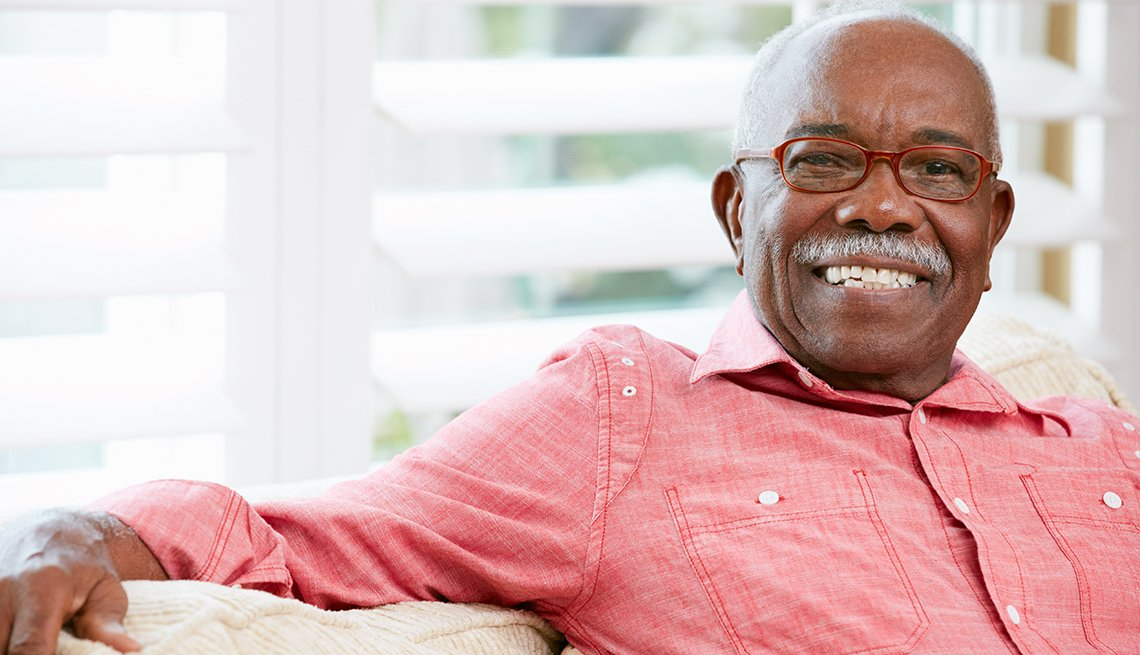 Smiling, mature African American man sitting in front of window