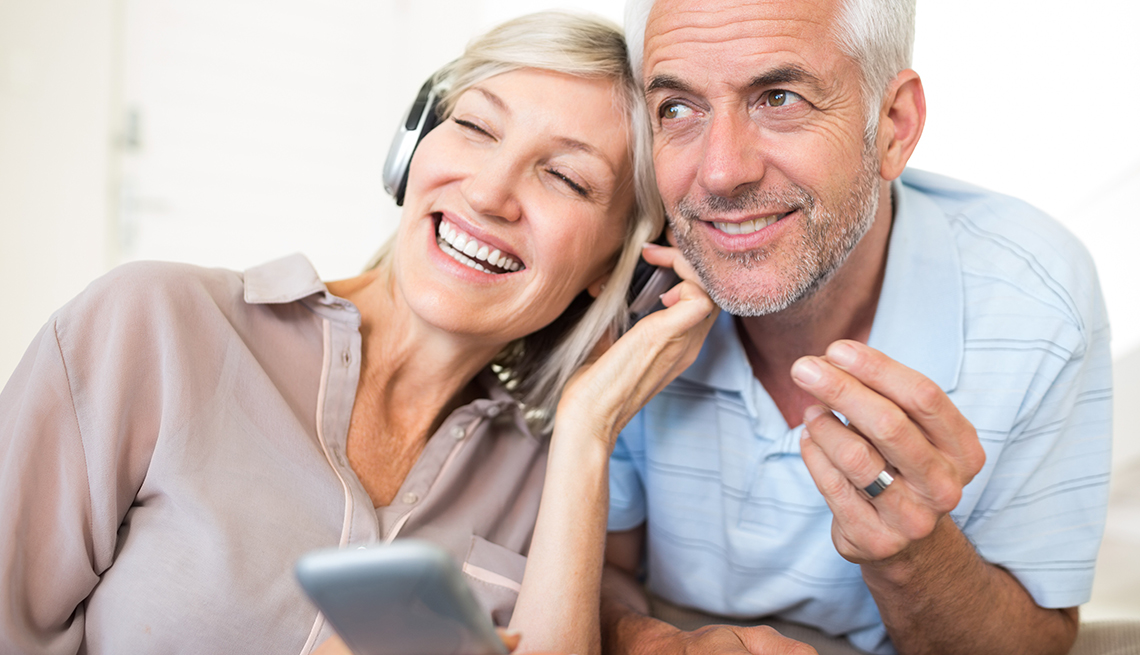 Mature couple simile listening to music on phone