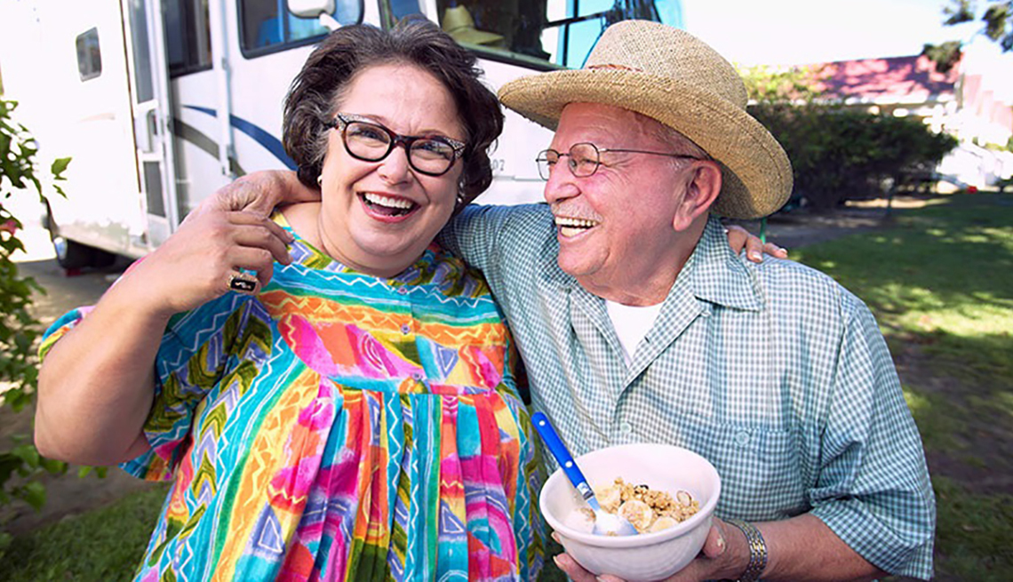 Mature couple wearing glasses, smiling, hugging in front of RV, man with bowl of cereal