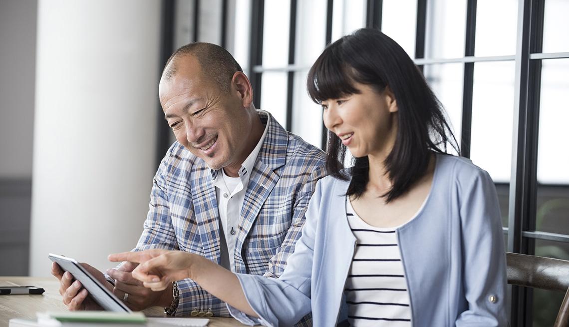 Asian man and woman looking at digital tablet.