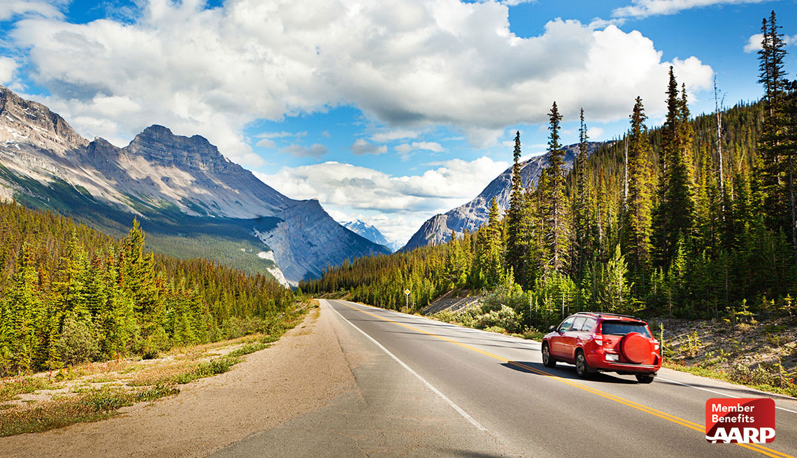 red car driving on road with blue sky and mountain in view