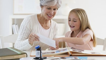 Grandmother and granddaughter working on scrap book at home
