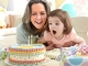 Grandmother and granddaughter blow out candles on a birthday cake