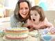 Abuela y nieta soplando una torta de cumpleaños