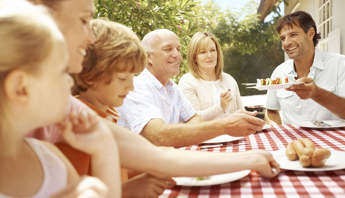 Family sitting around a table outside and eating, Life Insurance