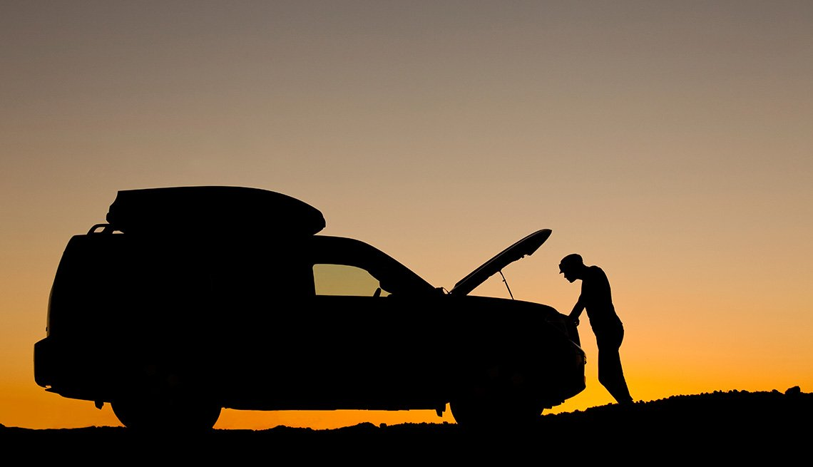 Man looking at engine at sunset.