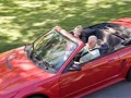 Couple in convertible car smiling, Road Trip