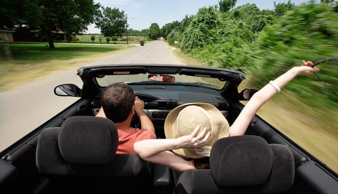 Una pareja en un auto convertible paseando