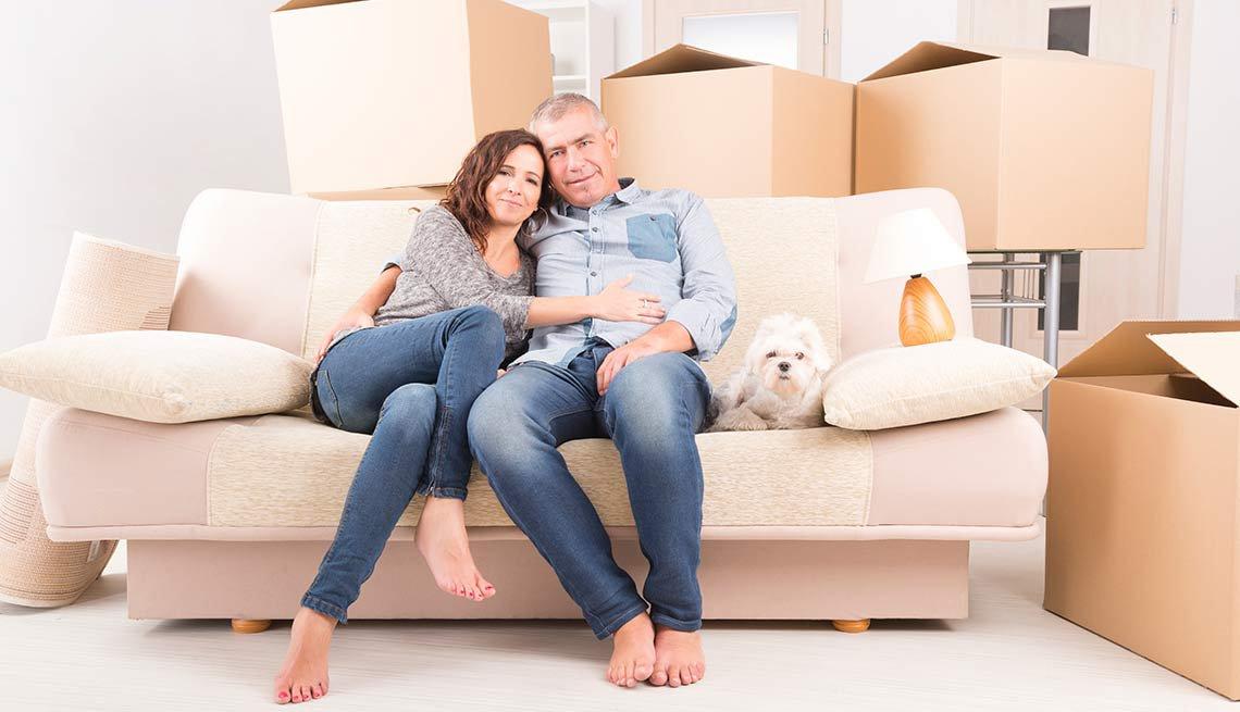 Una pareja sentada en un sofá en su nueva casa delante de cajones de cartón