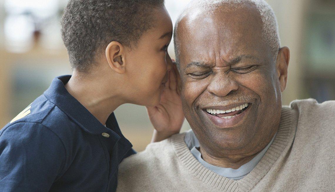 Un nieto afroamericano le susurra a su abuelo en el oíido