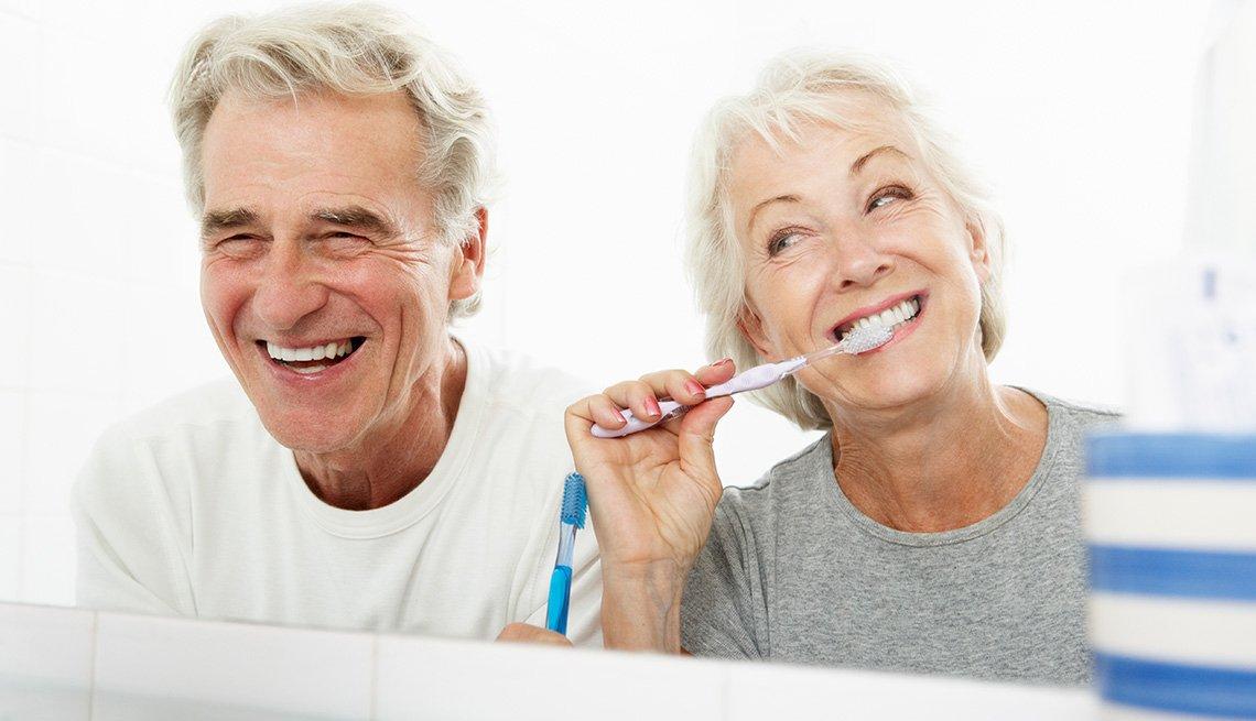 Una pareja de adultos cepillándose los dientes.
