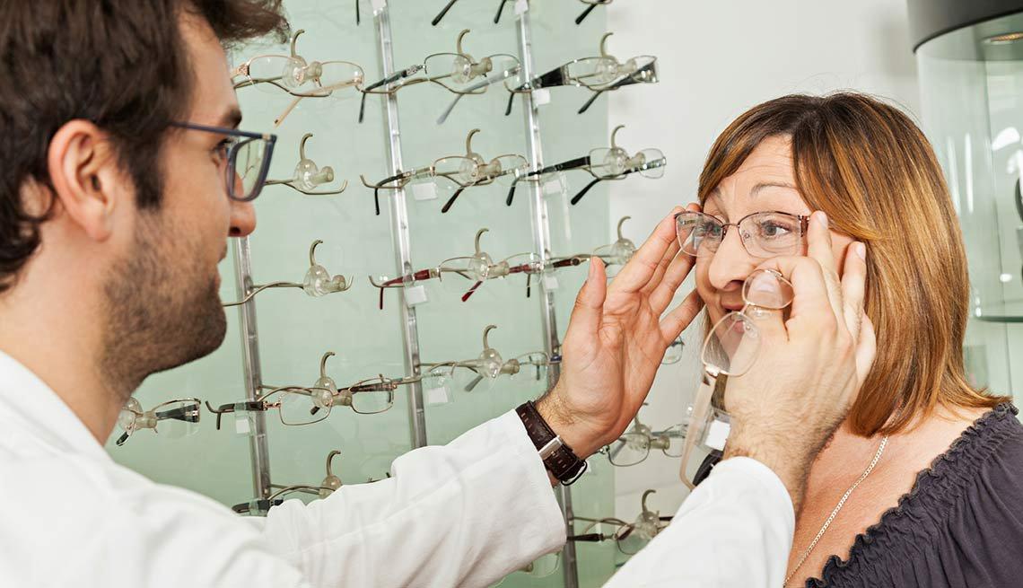 Una mujer se prueba lentes en una óptica con la ayuda de un empleado