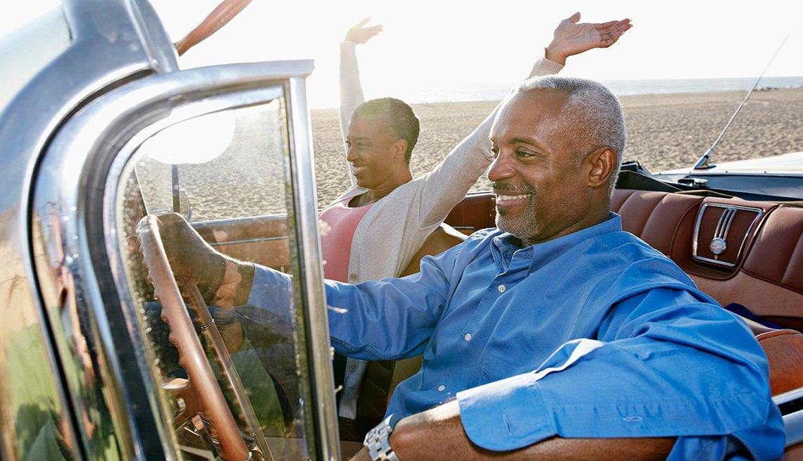 Pareja afroamericana en un auto convertible en la playa