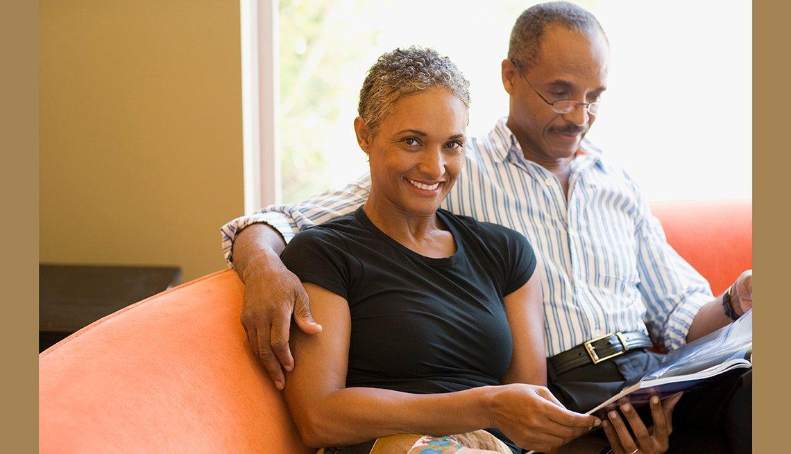 Una pareja afroamericana leyendo una revista en un sofá color rosa