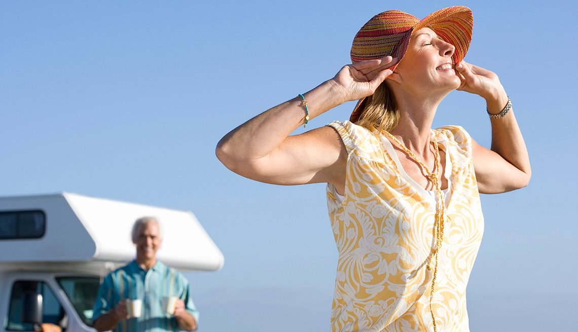Mujer madura con su esposo detrás frente a su vehículo en una playa