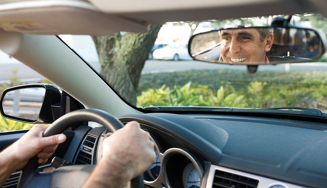 Un hombre sonriendo en su espejo retrovisor mientras conduce