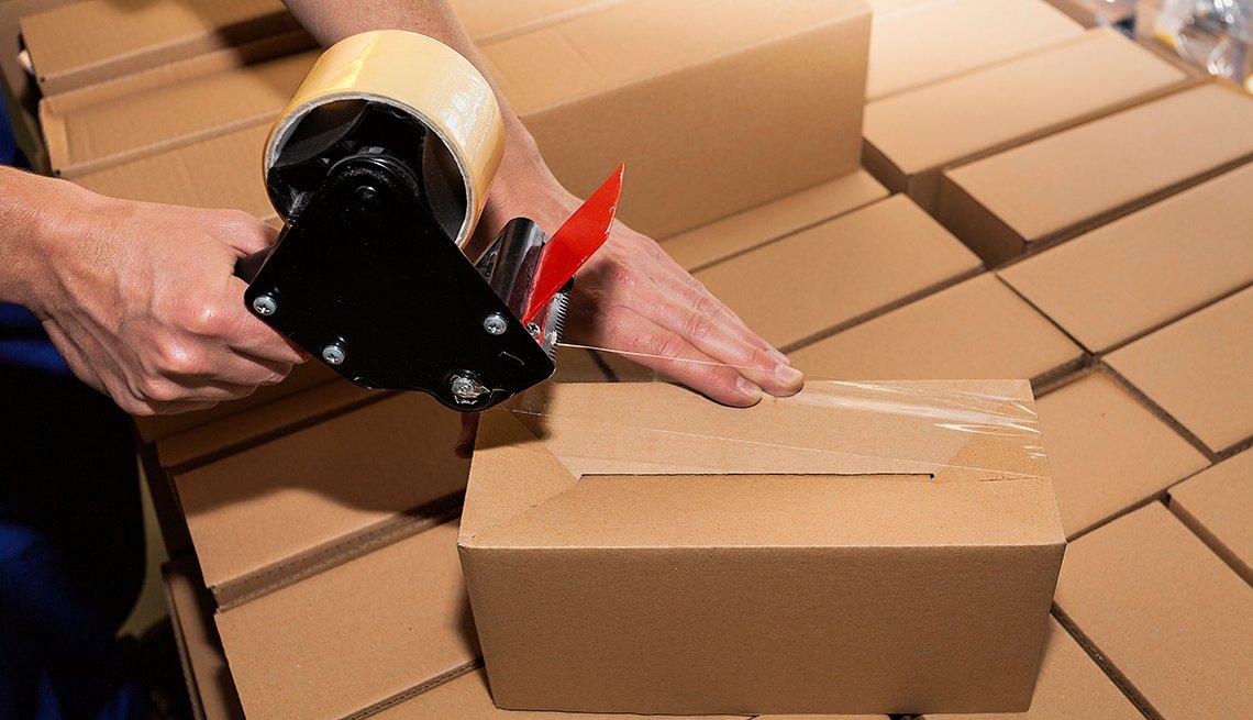 Un hombre sellando una caja encima de otro grupo de cajas