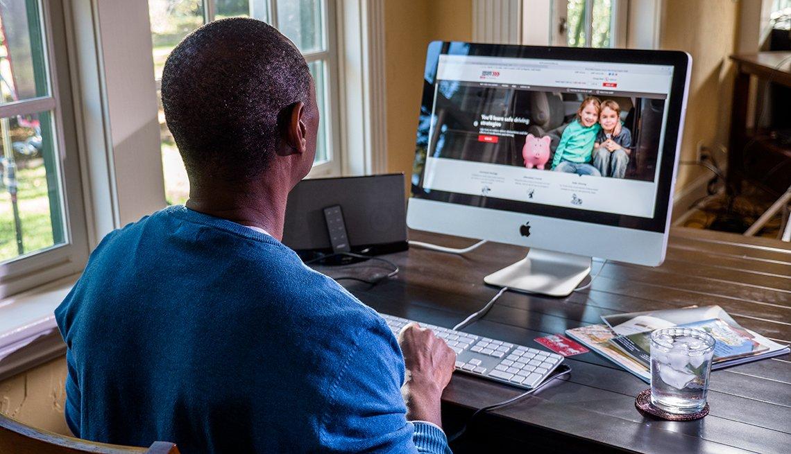 Un hombre afroamericano frente a su computadora Mac