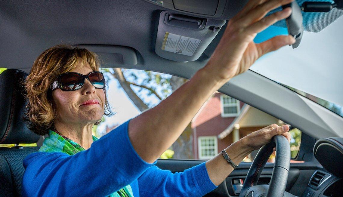 Una mujer ajustando el espejo retrovisor de su auto