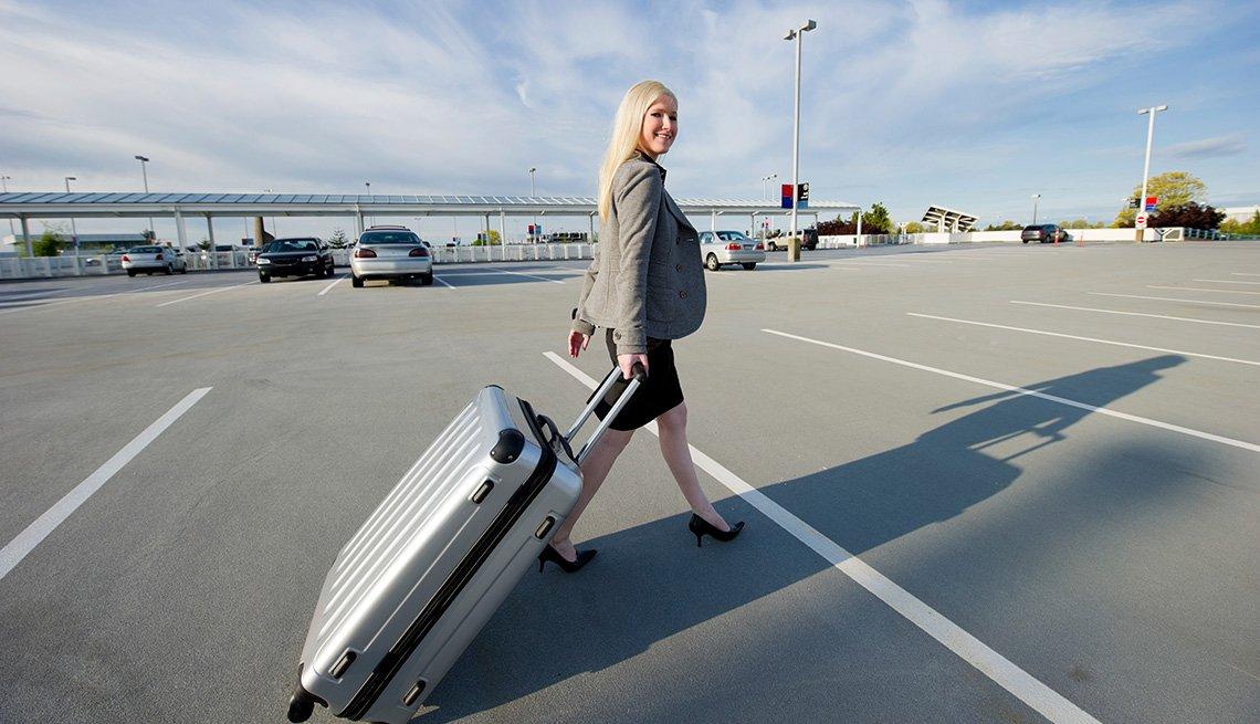 Una mujer con equipaje en el parqueo de un aeropuerto