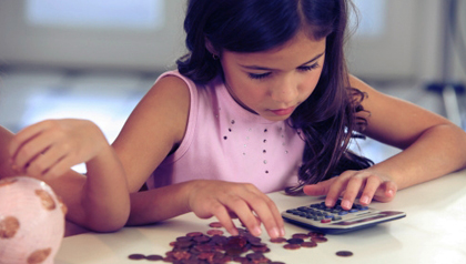 Young girl counting money with calculator