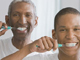 African American grandfather, father and son brushing teeth