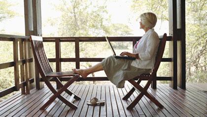 Mature woman on lodge verandah using laptop, side view