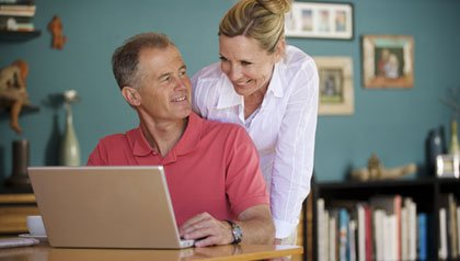 Senior couple with laptop at home