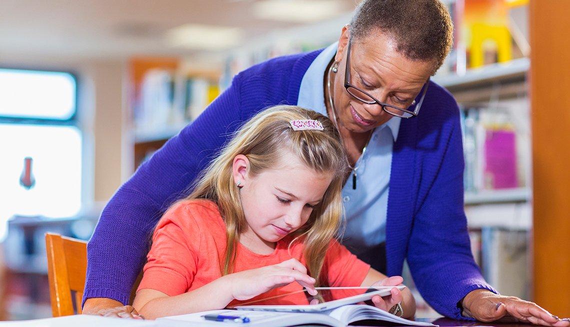 Mujer afroamericana ayudando a una niña a leer un libro en la biblioteca