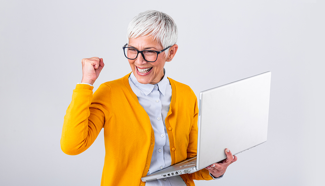 perks lady with yellow sweater fist pumping with laptop in hand