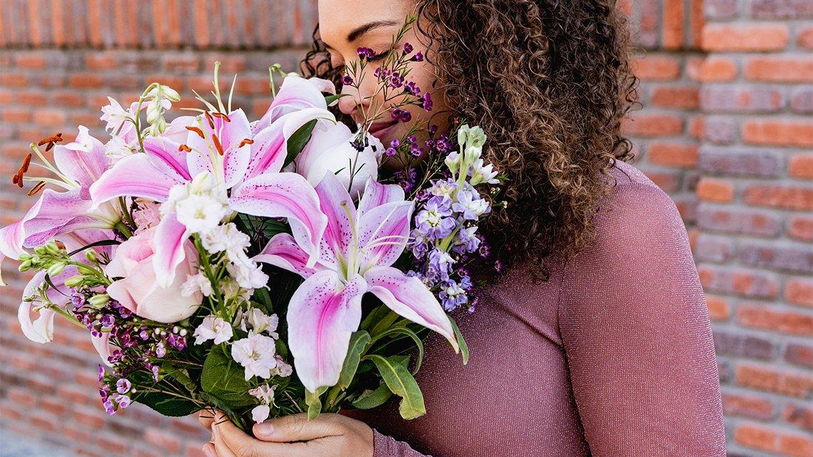woman holding a purple lillies bouquet