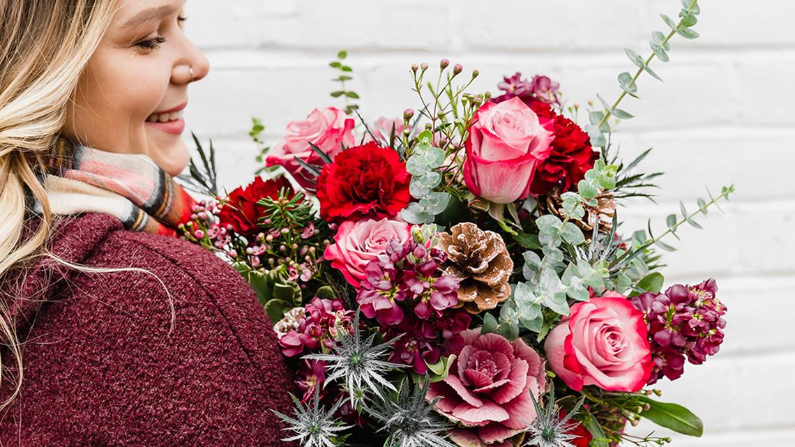 woman holding a winter themed flower bouquet