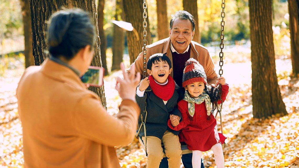 smiling man pushing 2 kids in swing