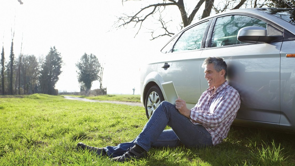 Mature man using digital tablet in countryside