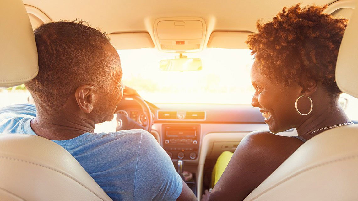 couple inside car smiling at sunset